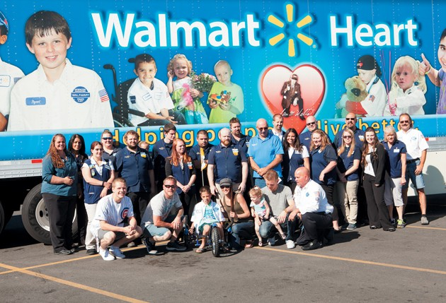 walmart employees pose for a group photo with kaden robinson and his family at the walmart heart event held for robinson on monday morning